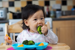 baby girl eating vegetable first time