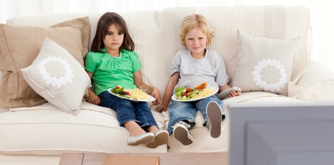 Cute Brother And Sister Having Dinner On The Sofa